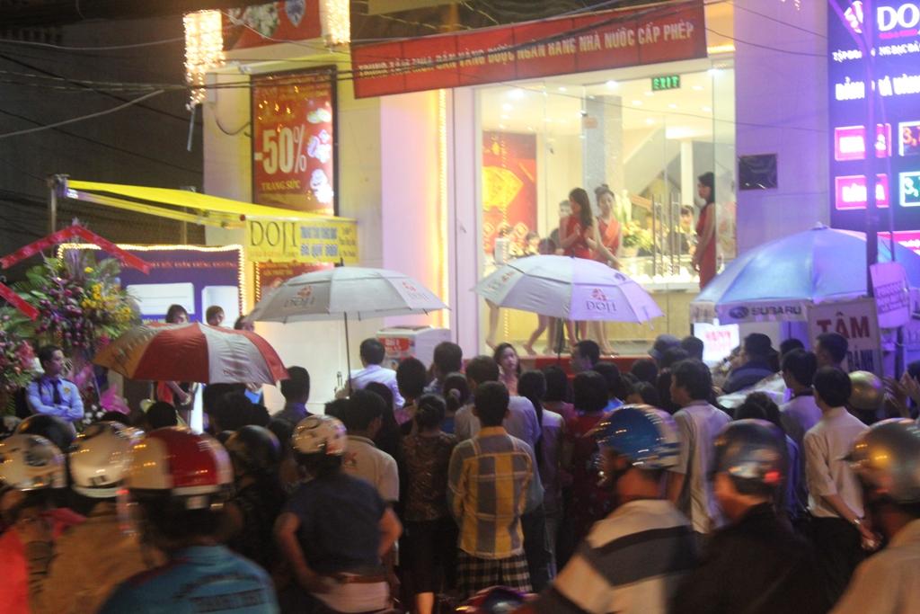 khách đứng tham gia chương trình dưới trời mưa ( có Ô DOJI)